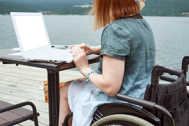 障害のある顔のない女性は屋外でラップトップを使用しています。リモートワーク、学習コンセプト。