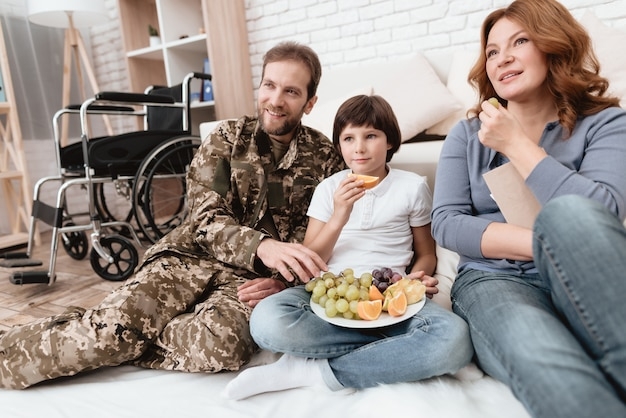 A disabled father in military uniform is eating fruits.