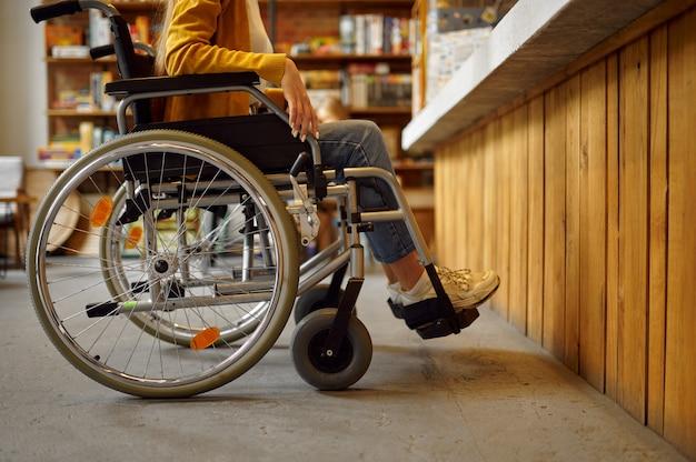 Студентка-инвалид в инвалидной коляске у стойки, инвалидности, книжной полки и университетской библиотеки или интерьера кафе на заднем плане. женщина-инвалид в колледже, парализованные люди получают знания