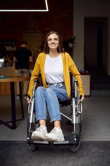 Студентка-инвалид в инвалидной коляске у окна, инвалидность, книжная полка и интерьер университетской библиотеки на заднем плане. молодая женщина-инвалид учится в колледже, парализованные люди получают знания