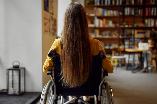 Студентка-инвалид в инвалидной коляске, вид сзади, инвалидность, книжная полка и интерьер университетской библиотеки на заднем плане. молодая женщина-инвалид учится в колледже, парализованные люди получают знания