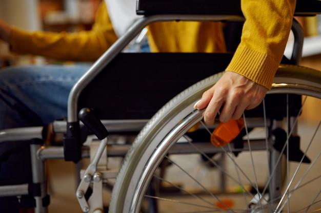 Студентка-инвалид в инвалидной коляске, инвалидности, книжной полке и интерьере университетской библиотеки на заднем плане. молодая женщина-инвалид учится в колледже, парализованные люди получают знания