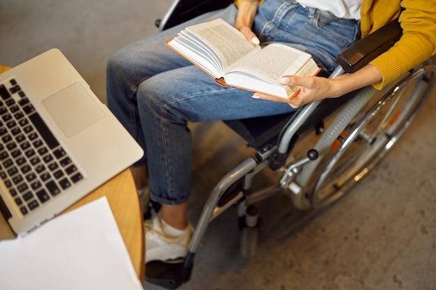 Студентка-инвалид в инвалидной коляске держит книгу, вид сверху, инвалидность, интерьер университетской библиотеки на заднем плане. женщина-инвалид учится в колледже, парализованные люди получают знания