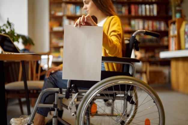 Студентка-инвалид в инвалидной коляске держит пустой бумажный лист, инвалидность, книжную полку и интерьер университетской библиотеки на заднем плане. женщина-инвалид в колледже, парализованные люди получают знания