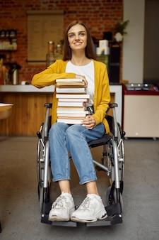Студентка-инвалид в инвалидной коляске держит стопку книг, инвалидность, интерьер университетской библиотеки на заднем плане. женщина-инвалид учится в колледже, парализованные люди получают знания
