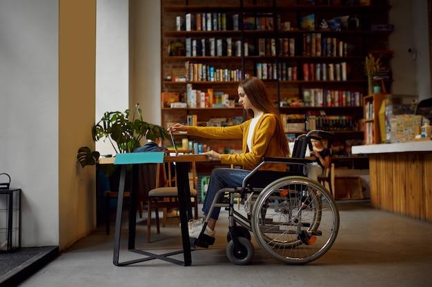 Студентка-инвалид в инвалидной коляске, использующая ноутбук, инвалидность, книжную полку и интерьер университетской библиотеки на заднем плане. молодая женщина-инвалид учится в колледже, парализованные люди получают знания