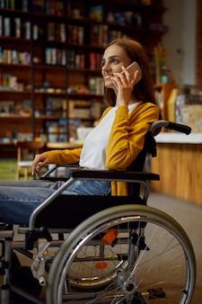 Студентка-инвалид в инвалидной коляске с помощью телефона, инвалидности, книжной полки и интерьера университетской библиотеки на заднем плане. молодая женщина-инвалид учится в колледже, парализованные люди получают знания