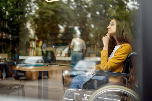 Студентка-инвалид в инвалидной коляске, вид из окна, инвалидность, книжная полка и интерьер университетской библиотеки на заднем плане. молодая женщина-инвалид учится в колледже, парализованные люди получают знания