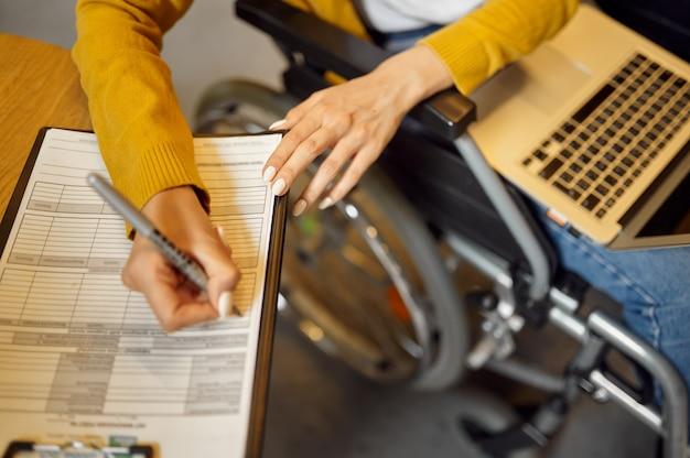 Студентка-инвалид в инвалидной коляске пишет в записной книжке, инвалидности, интерьере университетской библиотеки на заднем плане. женщина-инвалид учится в колледже, парализованные люди получают знания