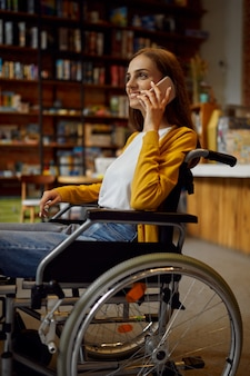 Disabled female student in wheelchair using phone, disability, bookshelf and university library interior on background. handicapped young woman studying in college, paralyzed people get knowledge