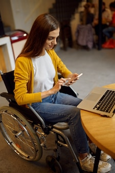 Disabled female student in wheelchair using phone