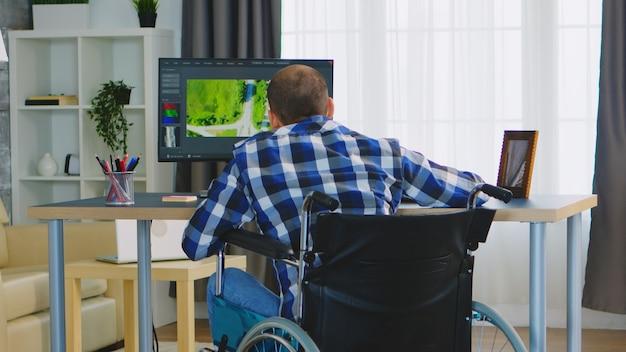 新しいビデオのポストプロダクションに取り組んでいる車椅子の障害者のフィルムメーカー。