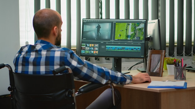 Disabled freelancer videographer editing postproduction a video project creating content sitting in wheelchair in modern company office. creator blogger working from modern photo studio.