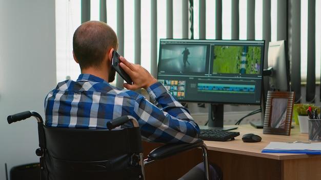 장애인 프리랜서 비디오그래퍼는 현대 회사 사무실에서 휠체어에 앉아 콘텐츠를 만드는 비디오 프로젝트를 편집하는 동안 전화로 이야기합니다. 사진 스튜디오에서 일하는 크리에이터 블로거.