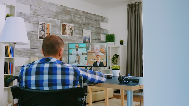 Disabled freelancer in wheelchair during a video call working from home.