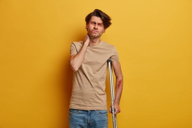 障害のある欲求不満の男性が首に触れ、脊椎に問題がある
