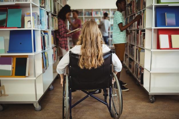Девушка-инвалид на инвалидной коляске в библиотеке