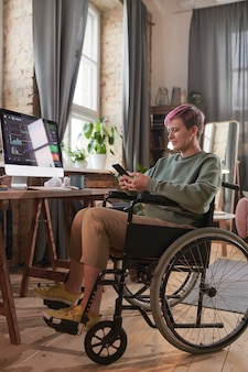 Disabled graphic designer sitting on wheelchair in front of her workplace with computer and talking online on the phone