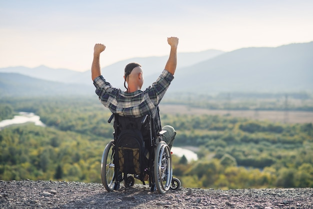 Парень-инвалид, сидящий в инвалидной коляске с поднятыми руками на горе в окружении красивых пейзажей