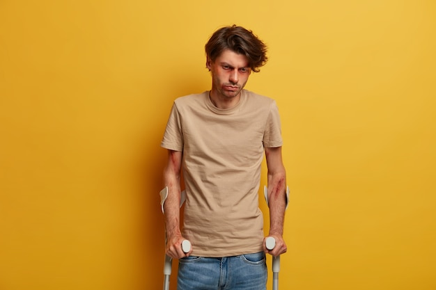 Disabled handicapped bruised man looks sadly down, cannot walk himself for long period of time, recalls dreadful road accident, becomes victim of reckless driving, poses against yellow wall