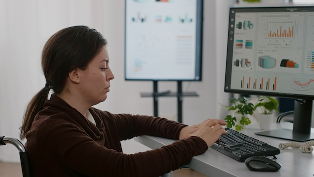 Деловая женщина-инвалид, обездвиженная в инвалидной коляске, работает над финансовым проектом, печатая на компьютере, показывая обрабатываемые данные на дисплее, сидя в офисе запуска бизнеса
