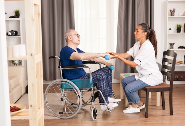 Disabled handicapped old person with social worker in recovery support therapy healthcare system