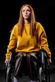 Disabled handicapped redhead woman sits looking up, dreaming, having thoughts. isolated black background