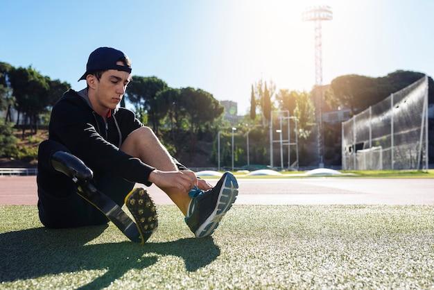 義足でトレーニングする準備ができている障害者の男性アスリート。パラリンピックスポーツコンセプト。