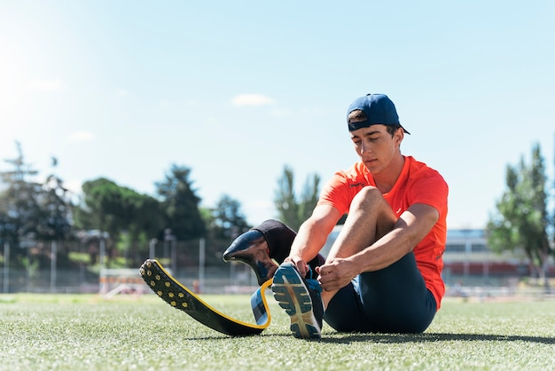 Disabled man athlete ready for training with leg prosthesis. paralympic sport concept.