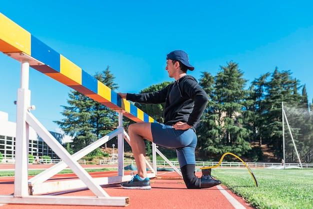 義足でストレッチする障害者アスリート。障害者スポーツの概念