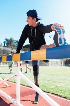 義足でストレッチする障害者アスリート。パラリンピックスポーツコンセプト。