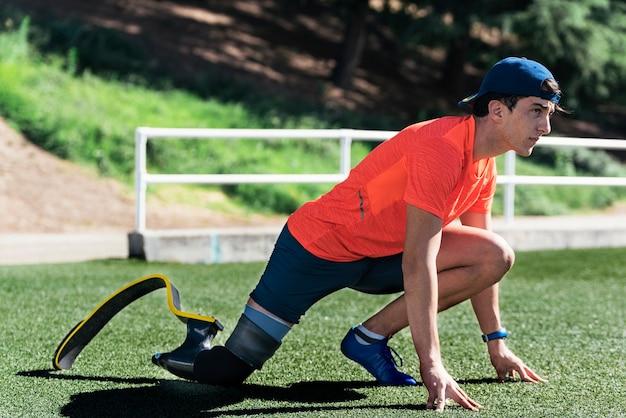 다리 보철물로 스트레칭 장애인 남자 선수. 패럴림픽 스포츠 컨셉.