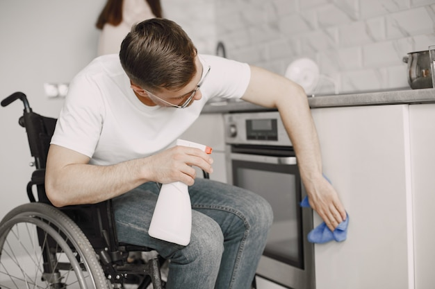 Disabled man cleaning the kitchen stove. impaired people