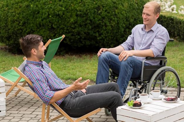 Человек-инвалид пьет кофе с другом