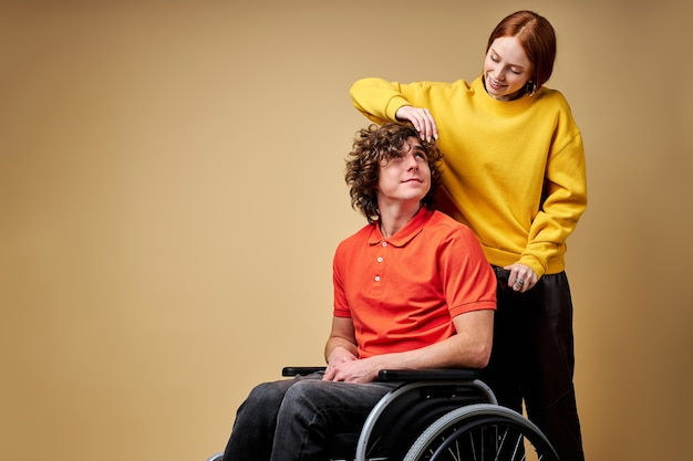 Disabled man enjoying time his beautiful kind girlfriend taking care of him touching his hair.