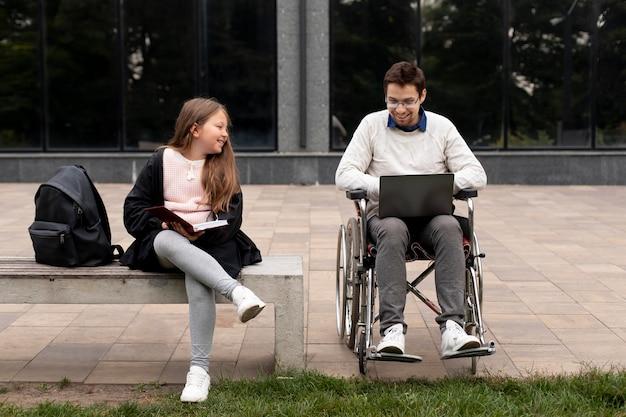 女の子が学ぶのを助ける障害者の男性