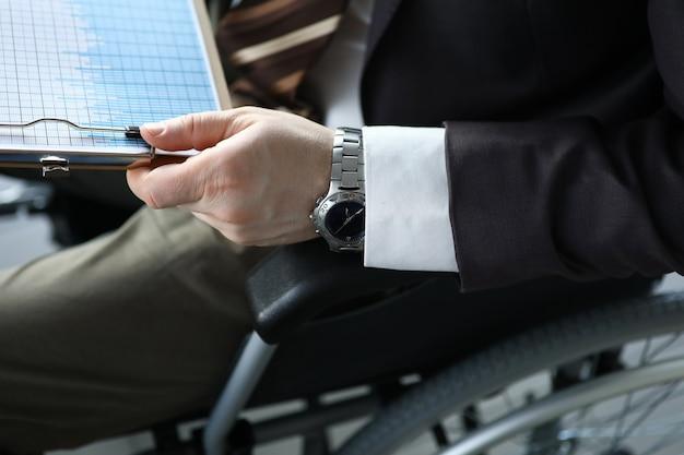 無効になっている男は座っている間ビジネスグラフを手に保持しています