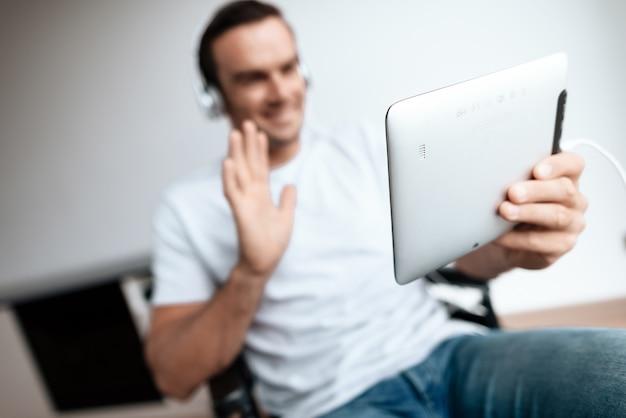 ヘッドフォンで無効になっている男は、タブレットを介して通信します。