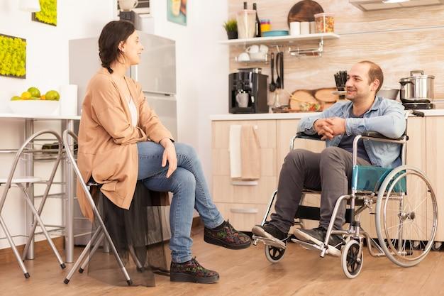 車椅子の障害者の男性と台所でお互いに微笑んでいる妻。事故後に統合した歩行障害のある障害者麻痺障害者。