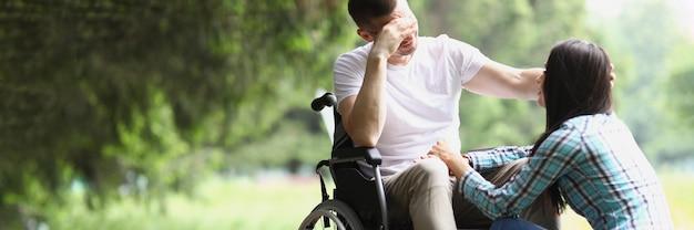 휠체어를 탄 장애인 남성이 공원에서 여성과 의사소통을 합니다.