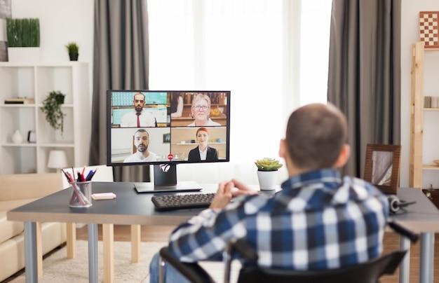 職場の同僚とのビデオ会議中に車椅子の障害者の男性。高度な技術を使用して、彼のアパートに座って、リモートで働いて、オンラインで彼のビジネスをしている若い固定化されたフリーランサー Premium写真