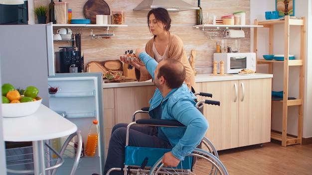 キッチンで妻を助ける車椅子の障害者の男性。冷蔵庫を開ける。麻痺障害者障害者愛と人間関係からの移動の助けを得ることが困難な