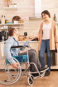 キッチンで彼の妻のために卵の箱を保持している車椅子の障害者の男性。事故後に統合した歩行障害のある障害者麻痺障害者。