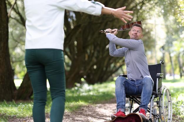 Мужчина-инвалид в инвалидной коляске размахивает скрипкой у женщины в парке, зарабатывая возможности для людей