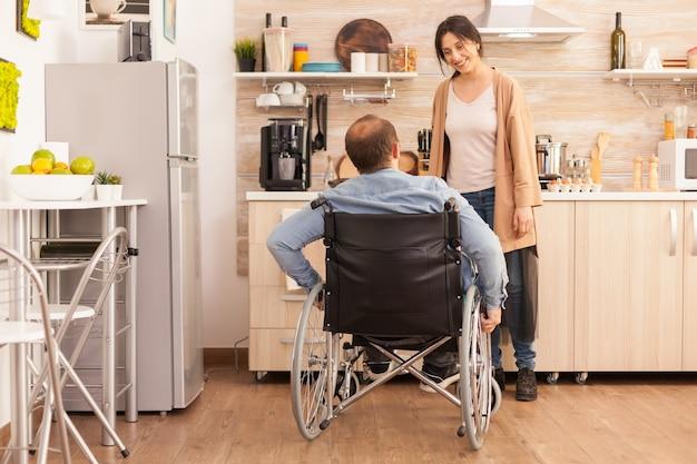 キッチンで笑顔で陽気な妻を見ている車椅子の障害者の男性。事故後に統合した歩行障害のある障害者麻痺障害者。
