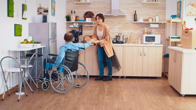 車椅子の障害者の男性は、妻が料理をしているときに冷蔵庫を開け、卵の箱を渡します。麻痺ハンディキャップ障害ハンディキャップ障害のある人が愛とrからモビリティの助けを得る