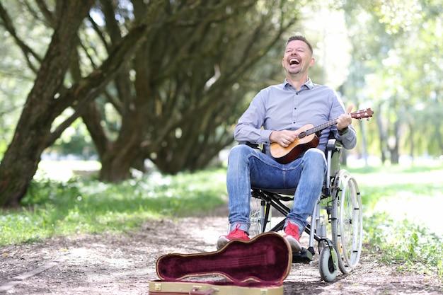휠체어를 탄 장애인이 공원에서 기타를 연주하고 돈을 거리 음악가를 장애인으로 만듭니다.