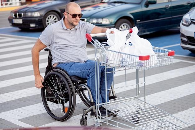 スーパーマーケットの駐車場で自分の前にカートを押す車椅子の障害者の男性