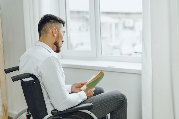 Человек-инвалид в инвалидной коляске, читающий зеленую книгу в помещении