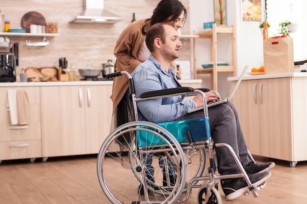 부엌에서 노트북을 사용하여 휠체어를 탄 장애인 남자와 아내가 옆에 서 있습니다. 사고 후 통합 보행 장애가 있는 장애인 마비 장애인.